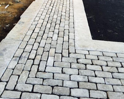 A stunning driveway border created from old granite cobblestones and reclaimed curbing