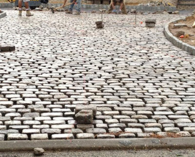 Installation of the used, antique cobblestones is part of the reclaiming experience