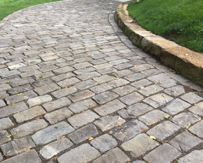 Reclaimed stone laid on side for a rustic cobblestone driveway