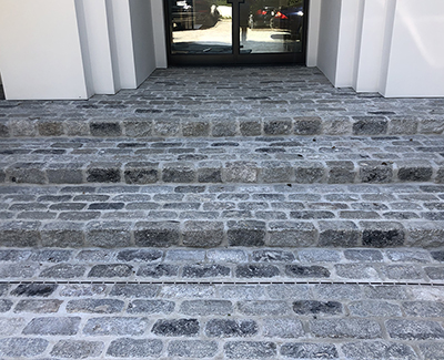 Entry steps created using salvaged regulation granite cobbles