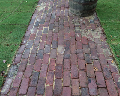 Old street bricks laid on side for sidewalk in historic community