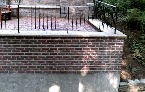 Salvaged bricks create a veneer on this patio retaining wall