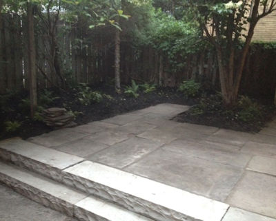 An urban reclaimed stone patio behind a restored historic home