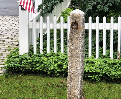 This antique hithcing post is wonderfully placed to highlight the surrounding landscape and picket fence.